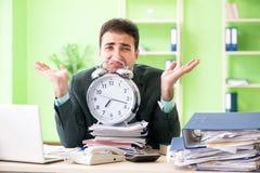 L'uomo d'affari arrabbiato con eccessivo lavoro che si siede nell'ufficio nel concetto della gestione di tempo Immagini Stock