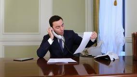 L'uomo d'affari arrabbiato ha una conversazione heated con qualcuno sul telefono della linea terrestre archivi video