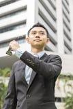 L'uomo d'affari asiatico decolla i suoi occhiali da sole i suoi occhiali da sole Fotografie Stock Libere da Diritti