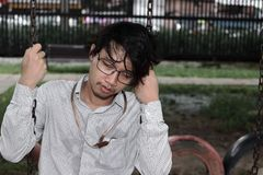 L'uomo d'affari asiatico depresso Tired si siede in parco concetto di affari di disoccupazione immagini stock libere da diritti