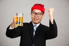L'uomo d'affari asiatico felice con il cappello del partito si ubriaca con la birra Fotografia Stock