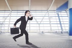 L'uomo d'affari asiatico sta correndo nel corridoio di arrivo fotografia stock
