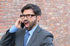 L'uomo d'affari assolutamente furioso grida nel telefono cellulare - immagine di riserva immagine stock libera da diritti