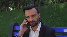 L'uomo d'affari attraente del tipo con una barba sta aspettando una telefonata mentre si sedeva su un banco di parco Uomo barbuto