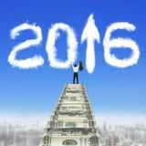 L'uomo d'affari aumenta la freccia 2016 di bianco delle scale dei soldi sulle nuvole Immagini Stock