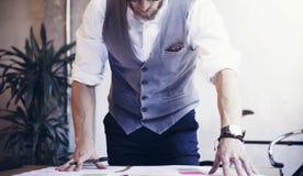 L'uomo d'affari barbuto Analyzes Business Plan del primo piano documenta il posto di lavoro moderno Giovane che lavora il legno S Fotografia Stock