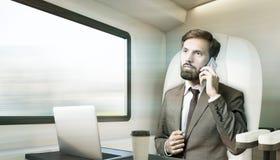 L'uomo d'affari barbuto sta parlando sul suo cellulare in treno, tonificato Immagini Stock