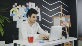 L'uomo d'affari barbuto sta scrivendo sul telefono in ufficio moderno video d archivio