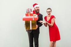 L'uomo d'affari barbuto tenendo molto il contenitore di regalo, donna mostra le sue mani Fotografie Stock