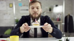 L'uomo d'affari barbuto triste, impiegato di concetto sta celebrando un compleanno solo nell'ufficio, lui sta soffiando una cande video d archivio