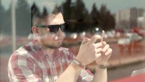 L'uomo d'affari bello in abbigliamento casual ed occhiali sta utilizzando un computer portatile che funziona in caffè Il tipo pia stock footage