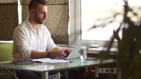 L'uomo d'affari bello in camicia ed occhiali classici sta utilizzando un computer portatile ed ha messo a fuoco mentre lavorava n stock footage