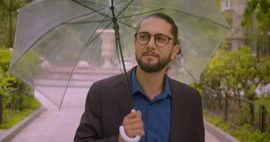 L'uomo d'affari bello dei pantaloni a vita bassa apre l'ombrello ed i sorrisi nella macchina fotografica che è soddisfatta nel pa archivi video