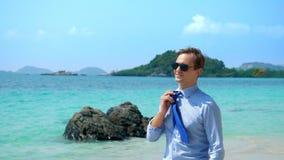 L'uomo d'affari bello in occhiali da sole ha camminato lungo una spiaggia tropicale, decollante il suo legame archivi video