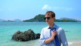 L'uomo d'affari bello in occhiali da sole ha camminato lungo una spiaggia tropicale, decollante il suo legame video d archivio
