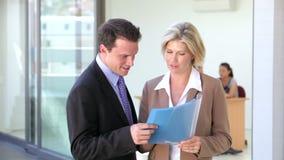 L'uomo d'affari And Businesswoman Meet e discute il rapporto video d archivio