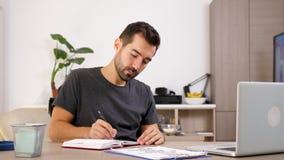 L'uomo d'affari a casa in abbigliamento casual con un computer portatile sullo scrittorio prende le note in un taccuino stock footage