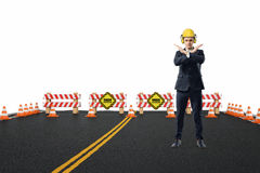 L'uomo d'affari in casco giallo e le cuffie che stanno sulla strada in costruzione con le sue armi hanno attraversato nella ferma Immagini Stock Libere da Diritti