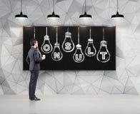 L'uomo d'affari che esamina consulta le lampadine Fotografia Stock Libera da Diritti