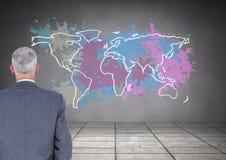L'uomo d'affari che esamina la mappa variopinta con pittura ha schizzato il fondo della parete Fotografia Stock
