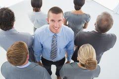 L'uomo d'affari che esaminano la macchina fotografica e l'affare team la condizione di nuovo alla macchina fotografica Immagine Stock