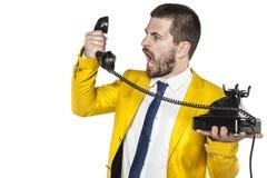 L'uomo d'affari che grida nel microtelefono del telefono, nervi ha esploso immagini stock