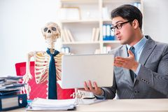 L'uomo d'affari che lavora con lo scheletro in ufficio Fotografia Stock