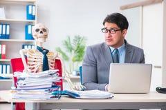 L'uomo d'affari che lavora con lo scheletro in ufficio Fotografie Stock