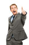 L'uomo d'affari che mostra i pollici aumenta il fondo di bianco del segno Immagini Stock