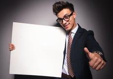L'uomo d'affari che mostra il bordo in bianco e fa il segno giusto fotografie stock