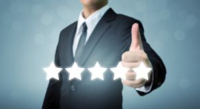 L'uomo d'affari che mostrano il pollice del segno della mano su e cinque star il simbolo alla i Immagine Stock Libera da Diritti