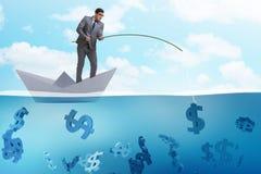 L'uomo d'affari che pesca i soldi dei dollari dalla nave di carta della barca fotografia stock