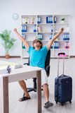 L'uomo d'affari che prepara per la vacanza nell'ufficio immagini stock