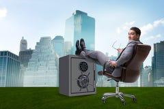 L'uomo d'affari che riposa mettendo gamba sulla cassaforte Immagine Stock Libera da Diritti