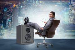 L'uomo d'affari che riposa mettendo gamba sulla cassaforte Immagini Stock