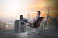 L'uomo d'affari che riposa mettendo gamba sulla cassaforte Fotografia Stock