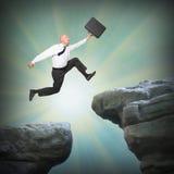L'uomo d'affari che salta dall'alta scogliera Immagini Stock