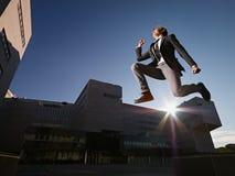 L'uomo d'affari che salta e che sorride fuori dell'ufficio immagine stock