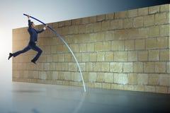 L'uomo d'affari che salta sopra il brickwall nel concetto di affari Fotografia Stock