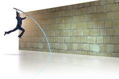L'uomo d'affari che salta sopra il brickwall nel concetto di affari Immagini Stock