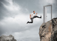 L'uomo d'affari che salta sopra le montagne per raggiungere una porta Fotografie Stock Libere da Diritti