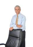 L'uomo d'affari che si appoggia sopra appoggia della sua presidenza Fotografie Stock