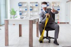 L'uomo d'affari che si esercita con i vetri d'uso del vr dell'estensore elastico Immagini Stock