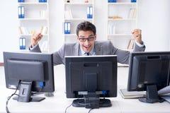 L'uomo d'affari che si siede davanti a molti schermi Immagine Stock Libera da Diritti