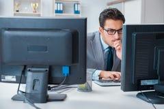 L'uomo d'affari che si siede davanti a molti schermi Immagini Stock
