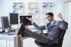 L'uomo d'affari che si siede davanti a molti schermi Fotografia Stock
