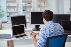 L'uomo d'affari che si siede davanti a molti schermi Immagine Stock