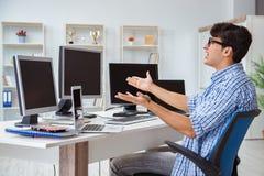L'uomo d'affari che si siede davanti a molti schermi Fotografie Stock