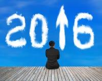 L'uomo d'affari che si siede sul pavimento di legno con il segno 2016 della freccia si appanna Fotografia Stock