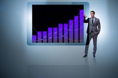 L'uomo d'affari che sta accanto al computer della compressa nel concetto di affari Immagini Stock